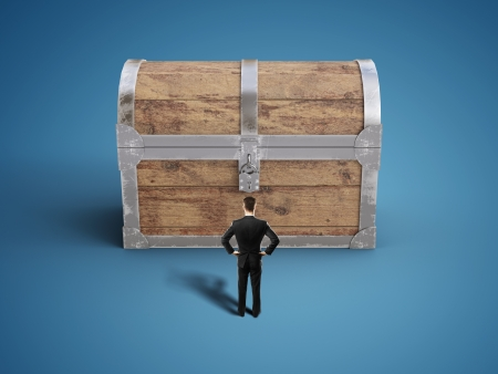 businessman looking at old antique chest on blue background Stock Photo - 21352405