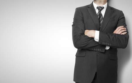 businessman standing  with hands  folded on wall background Stock Photo - 21352416
