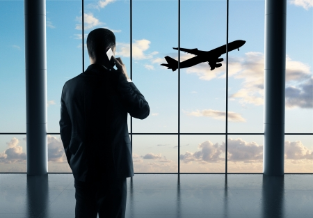 businessman with phone and airplane in sky