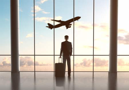 businessman in airport with luggage and looking in airplane Stock Photo - 21349532