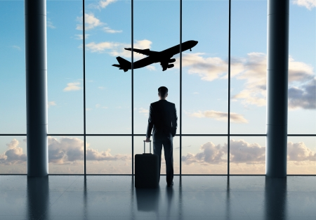 man in airport with luggage and looking in airplane photo