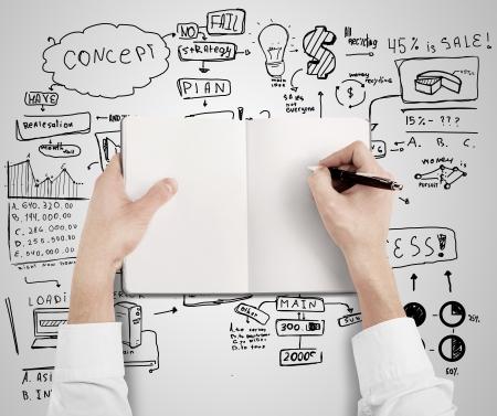 handen tekenen in het boek op een bedrijfsstrategie achtergrond