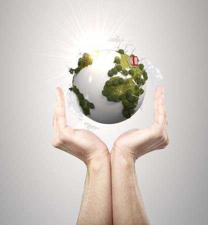 灰色の背景に地球を保持手します。