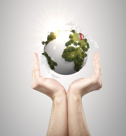 hands holding earth on gray background