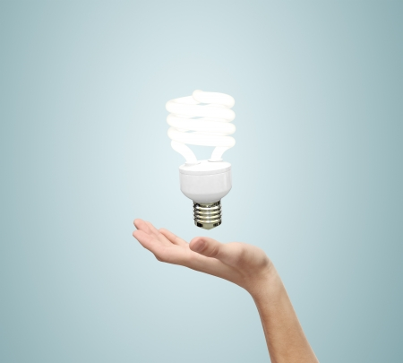 hand and energy saving lamp on a blue background photo