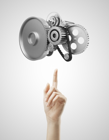 rack wheel: hand pointing at metal gears and cogs wheels Stock Photo