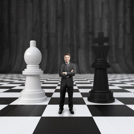 businessman standing on chessboard with chess photo