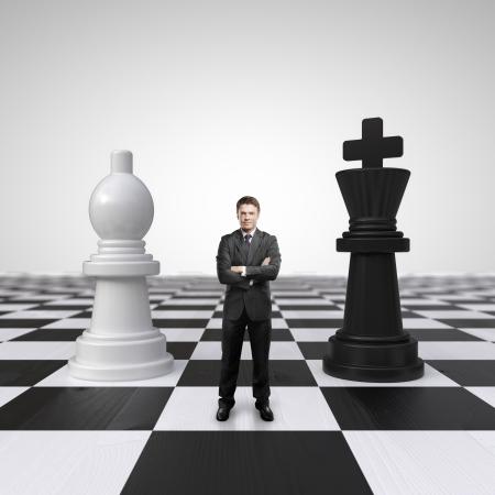 pensamiento estrategico: joven hombre de negocios de pie en el tablero de ajedrez con el ajedrez