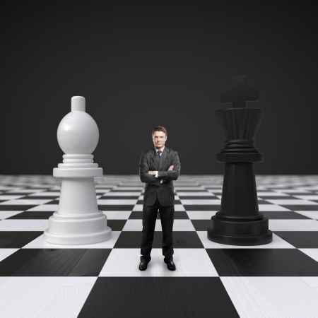 young man standing on chessboard with chess photo