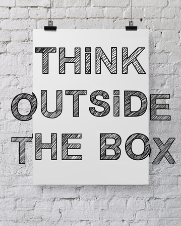 paper poster with drawing think outside the box on brick wall photo