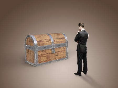 businessman looking at old antique chest on brown background photo