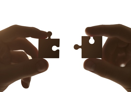 two hands collect puzzle on a white background photo