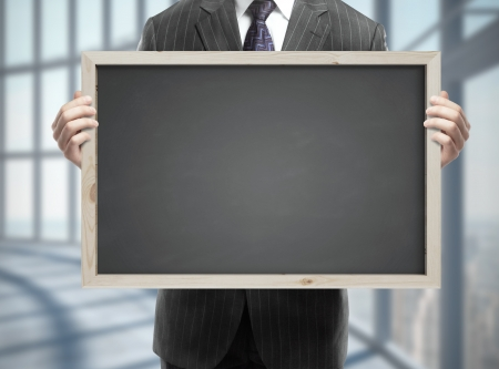 businessman in suit holding blackboard with business concept in office Stock Photo - 21689884