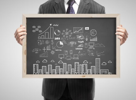 businessman in suit holding blackboard with business concept Stock Photo - 21689886