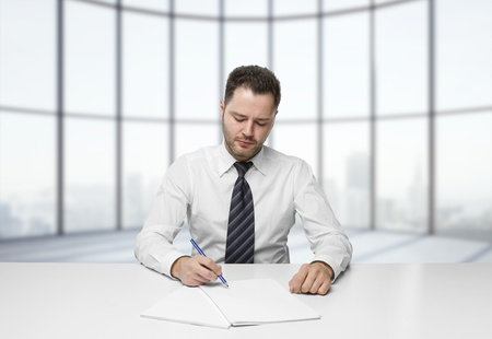 businessman writing on paper sitting at table photo