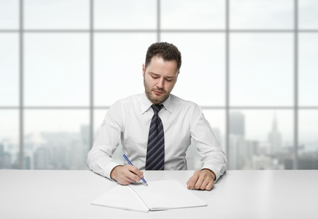 businessman writing on paper sitting at table in office photo