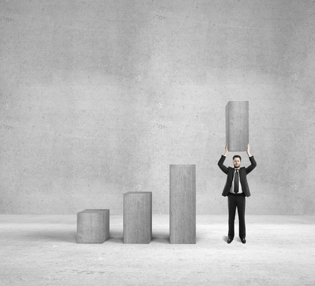 incentive: businessman holding column in concrete background Stock Photo