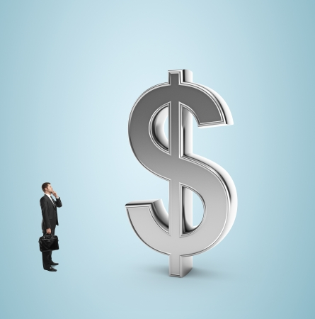 businessman with briefcase looking at dollar symbol on a blue background photo