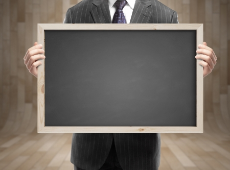 businessman in suit holding blank blackboard in office Stock Photo - 21693018