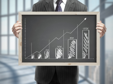businessman in suit holding blackboard with chart in office Stock Photo - 21693019