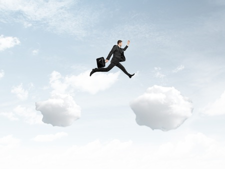 businessman jumping from cloud to another cloud photo