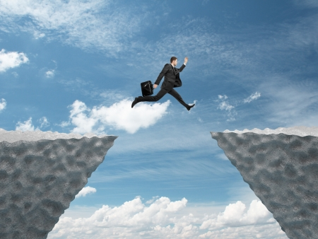 businessman jumping: businessman jumping from rock to another rock