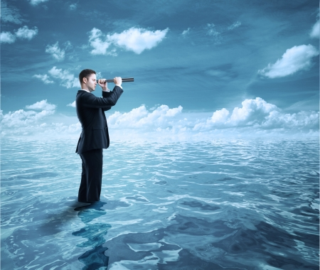 businessman standing in ocean and  looking through a telescope photo