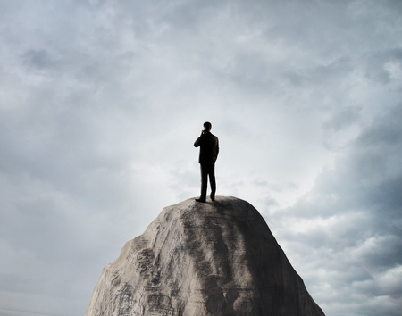 businessman standing on rock with phone photo