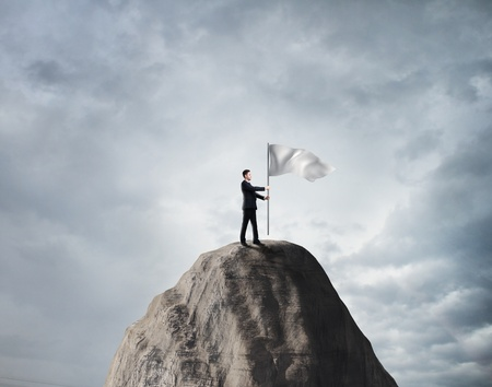 businessman standing on rock with white flag Stock Photo - 22087773