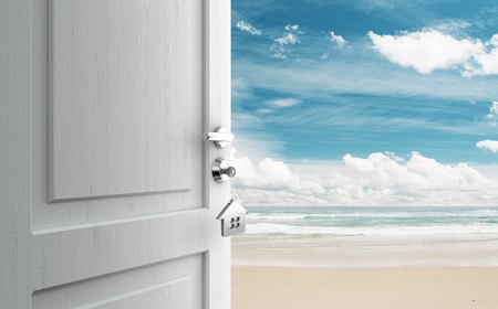 key to freedom: opened door with key in lock in beach