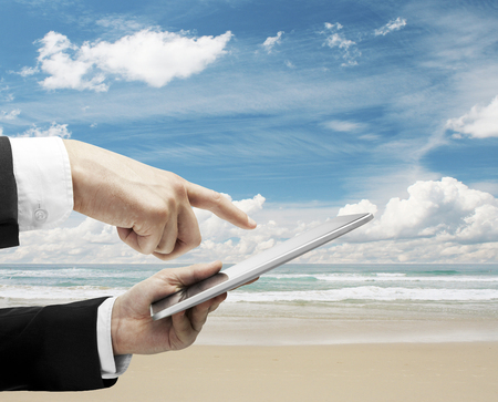 hand holding and pusning tablet  on ocean backgrounds photo