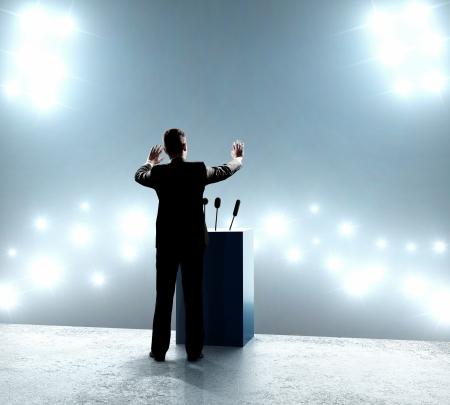 hablar en publico: hombre de negocios de pie en el podio y se cierra sobre los brotes