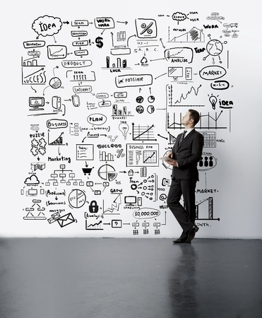 young man lookig at drawing business concept on wall photo