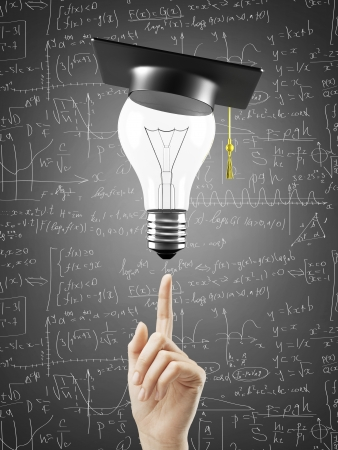 hand pointing at lamp with graduation hat photo