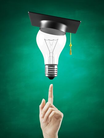 hand pointing at lightbulb with graduation hat photo