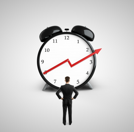 businessman looking at clock with growth red  arrow Stock Photo