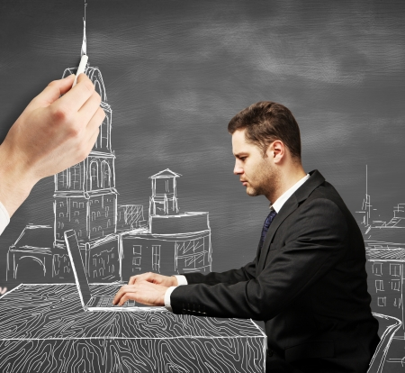 Businessman sitting at drawing  table with a laptop Stock Photo - 22470937