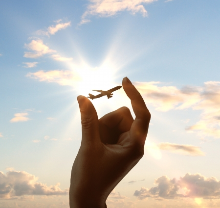 airplanes: hand holding airplane on sky background Stock Photo