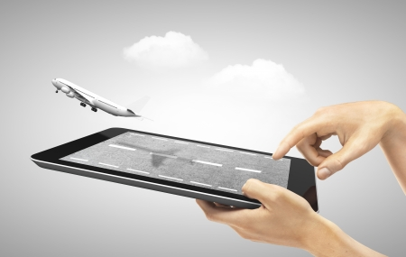 hands holding touch pad with fly airplane Stock Photo
