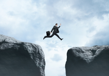 abyss: businessman jumping  from rock to rock Stock Photo