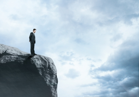 abyss: businessman standing at big rock Stock Photo