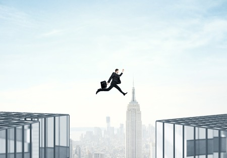 businessman jumping: businessman jumping from roof to roof on city