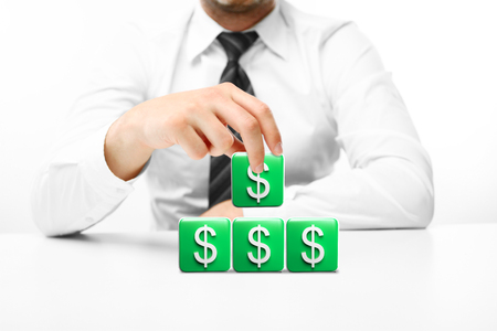 building blocks business: man building a house out of blocks, business concept Stock Photo