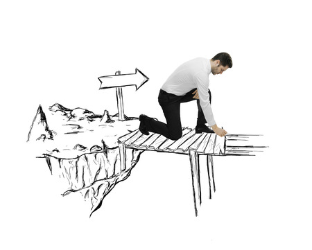 difficult journey: young man drawing abstract bridge the gap Stock Photo