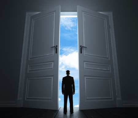 success concept: young man in room with big door to sky