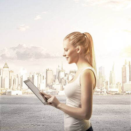 lady with  touch pad on city background photo