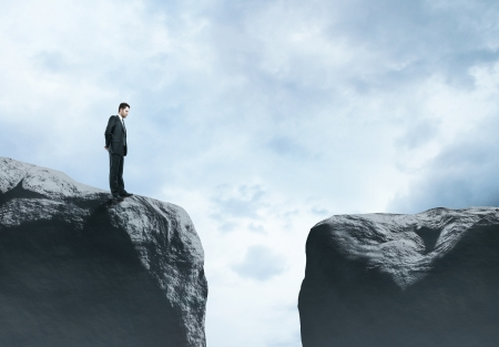 difficult journey: businessman standing at big rock Stock Photo