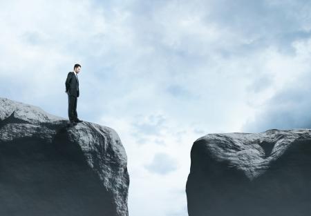 businessman standing at big rock
