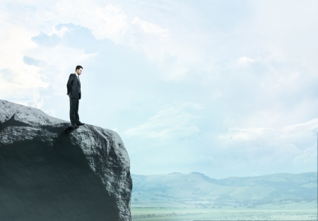 abyss: businessman in suit standing at big rock