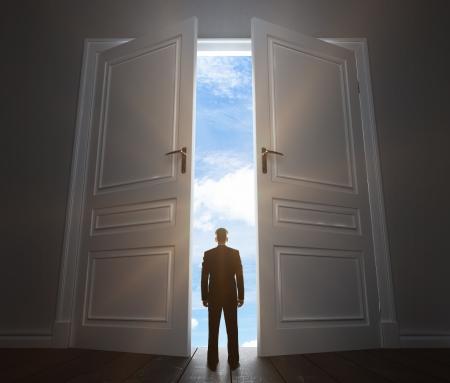 young man in room with big door to sky photo